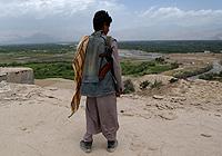 在遣散过程中,前儿童兵穆罕默德•阿明站在位于阿富汗巴格拉姆残破的军营屋顶远眺着乡村。