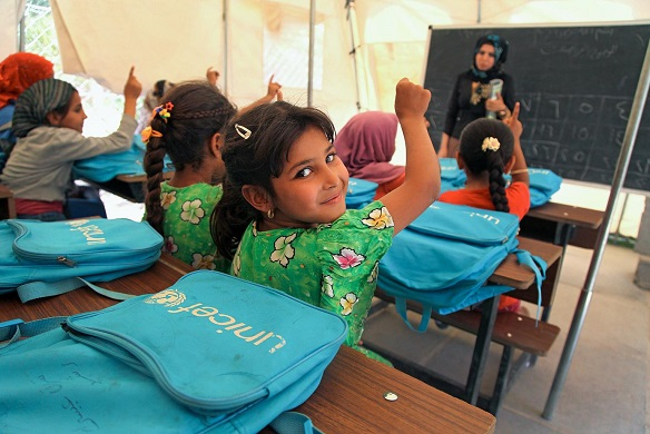 On 16 June a student raises her hand to answer a question from her teacher Hiba Ahmed in a tent classroom at the Al-Takya Al-Kaznazaniya school in Al-Takya Al-Kaznazaniya IDP camp, near Baghdad.